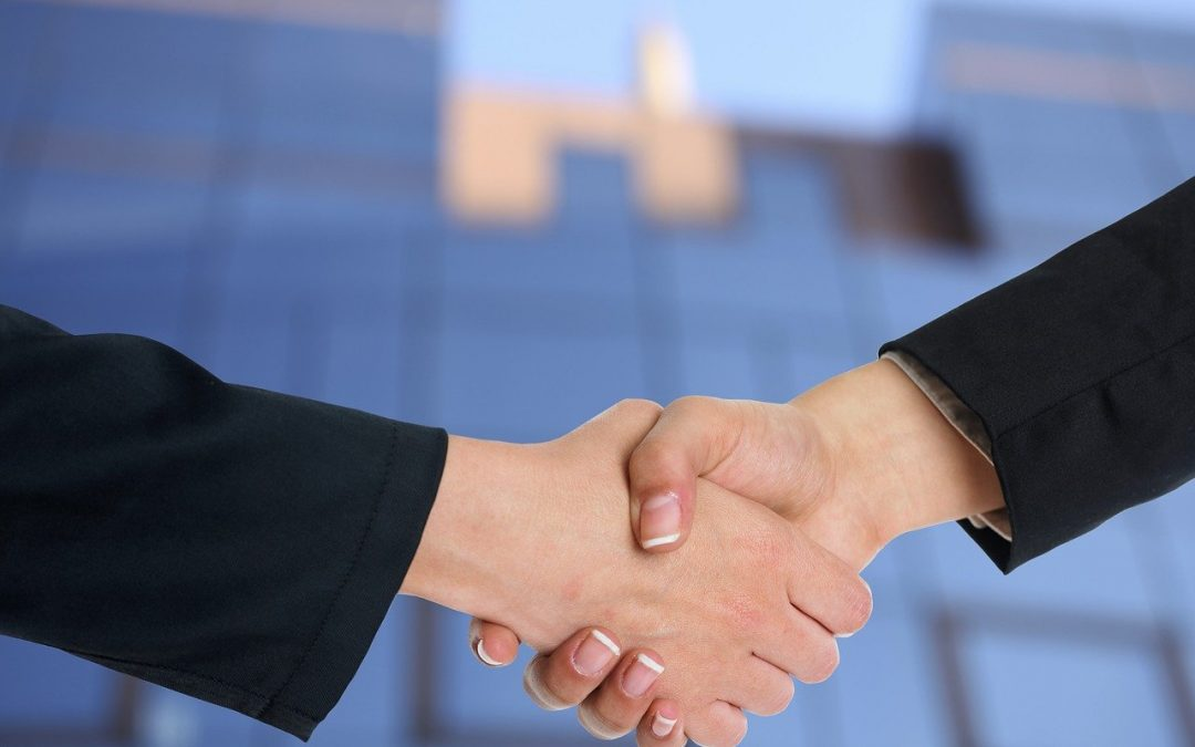 Two businesspeople shake hands in an office